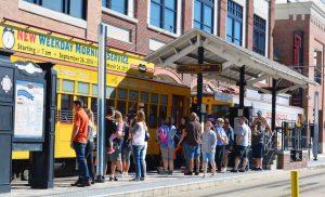 passengers wait to board a streetcar