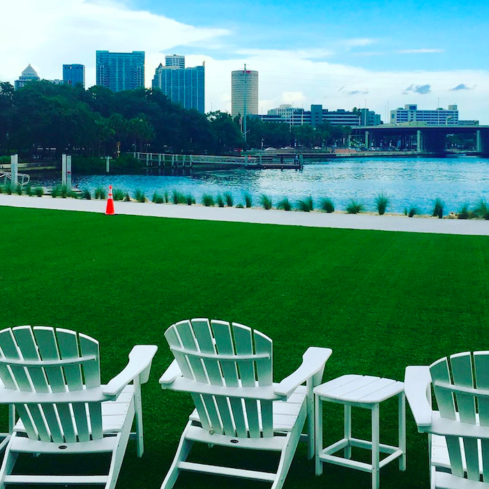 Photo shows lawn chairs on park grass looking out towards the Tampa skyline