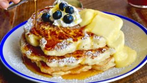 Stack of pancakes covered in syrup and blueberries