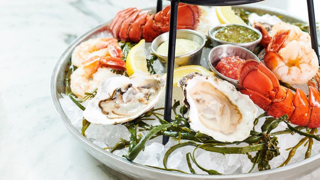 Photo of raw oysters and lobster tails over ice