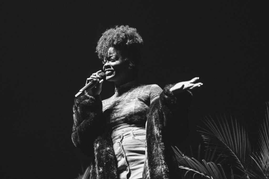 A black and white photo of Ari Lennox singing into a microphone