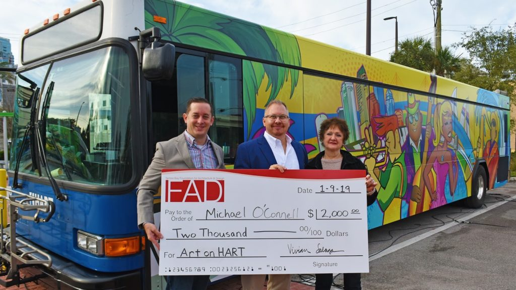 Photo of bus with a giant colorful mural painting on it.