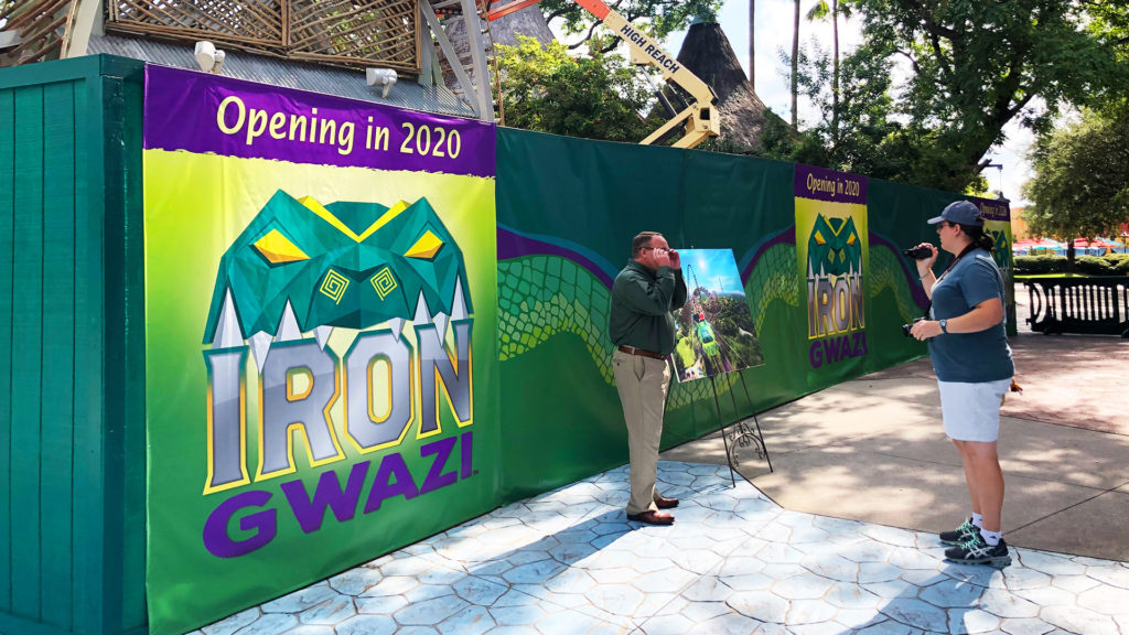 A sign for Iron Gwazi on a green construction fence in front of the rollercoaster under construction