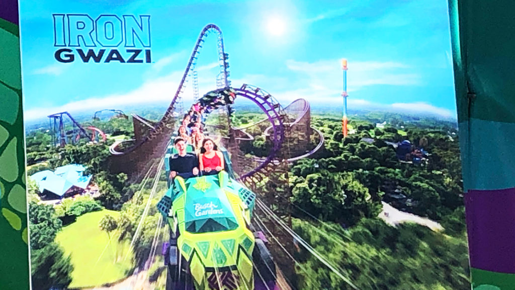 A rendering of Iron Gwazi showing riders coming out a fast loop near the top of the future rollercoaster