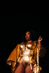 Lizzo posing while on stage performing