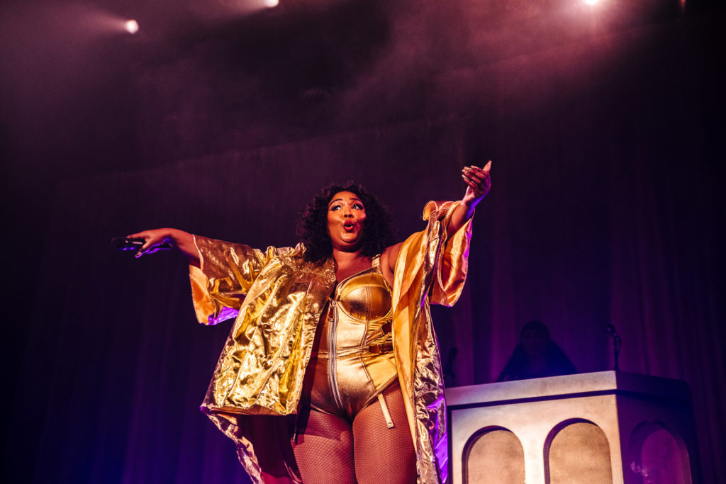 Lizzo gesturing to the crowd during her concert to sing along with her