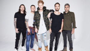 Band members of We The Kings posing side by side in casual clothes on a gray background