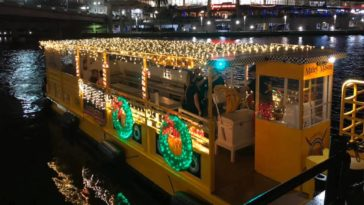 A yellow water taxi covered in Christmas Lights