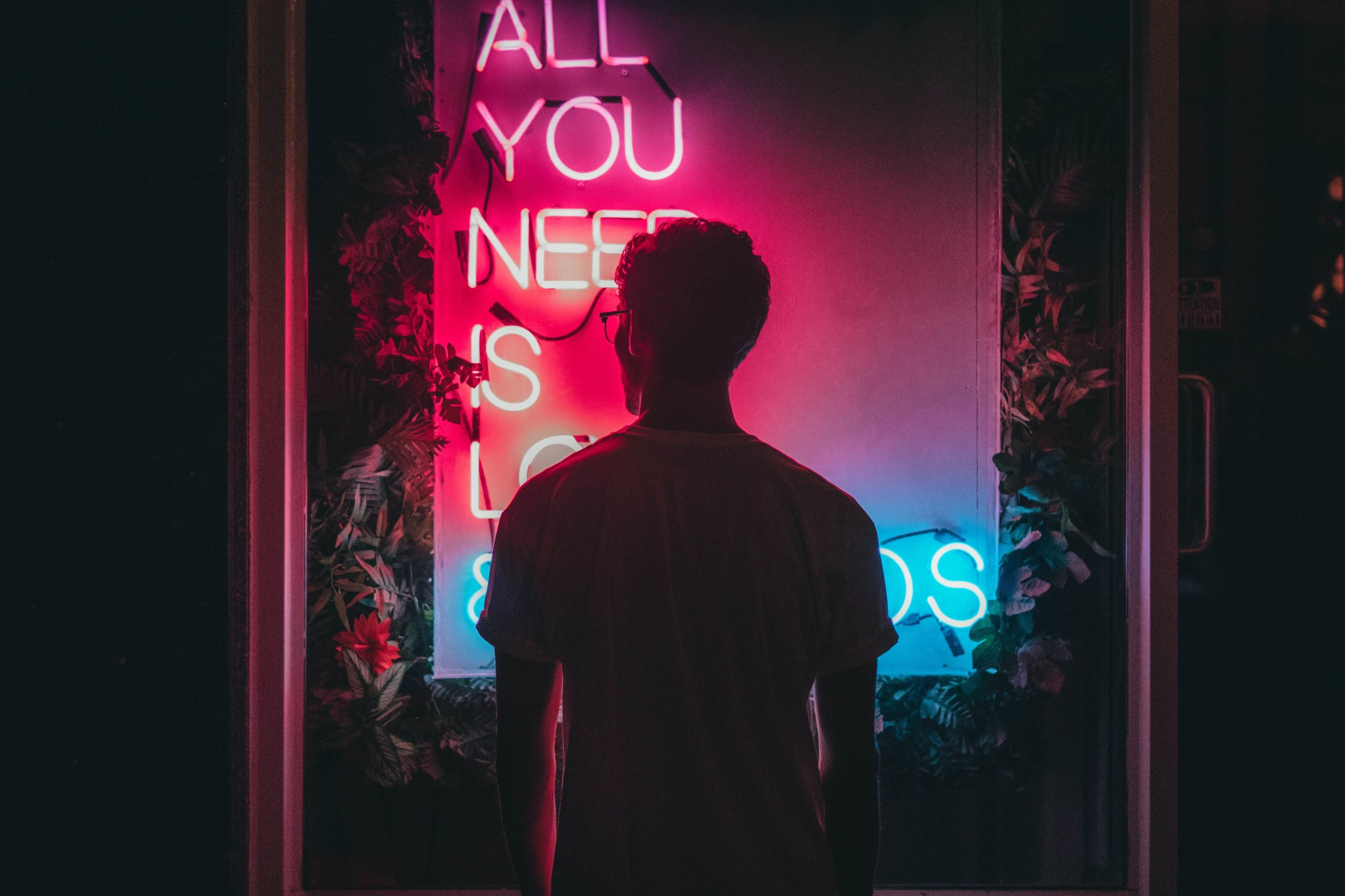 image of silhouette of man standing in front of neon lights