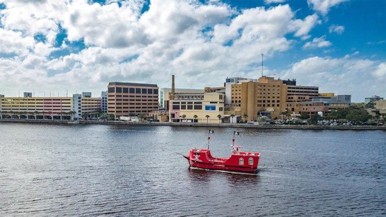 Photo of a red pirate ship in the water outside a downtown area