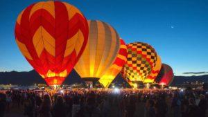 Photo of hot air balloons glowing at night
