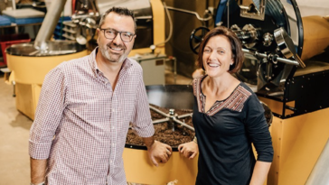 Photo of Kahwa Coffee owners posing in front of roaster