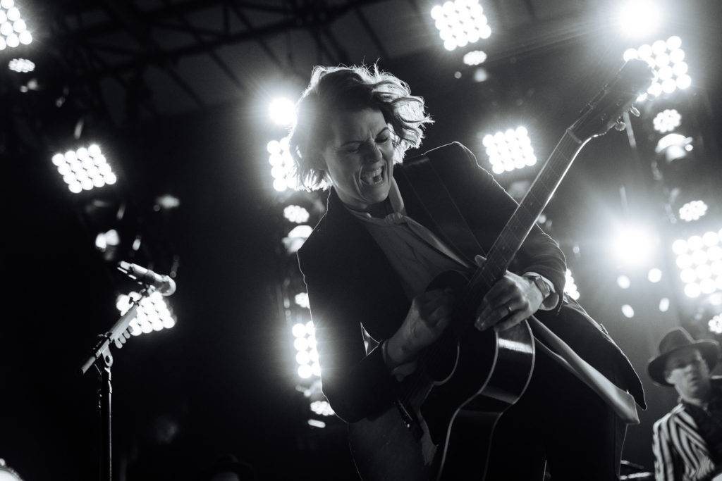 Brandi Carlile with hair flowing and a giant grin as she plays her guitar in motion