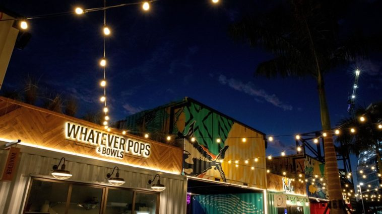 Night photo of repurposed shipping containers at an outdoor food hall