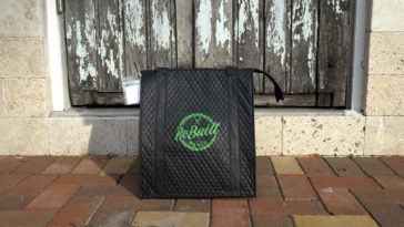 A black rebuilt meals insulated bag sitting in front of a wooden front door of a house