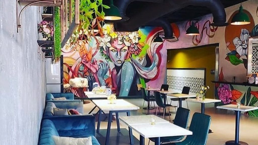 vibrant pink and purple mural inside a small restaurant