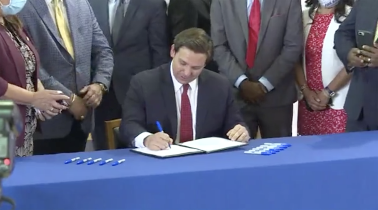 Photo of governor signing a bill at a blue table
