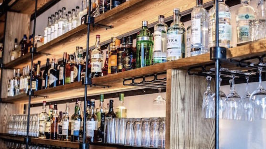 Inside a bar with an assortment of liquors on display