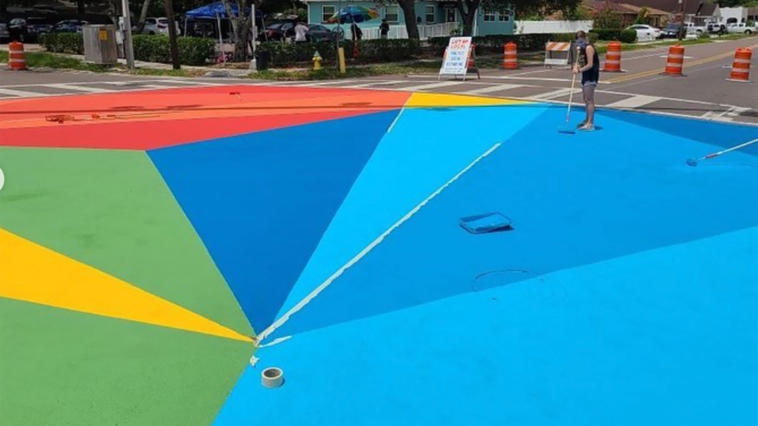 Photo of a street mural with geometric blue, green, and yellow patterns