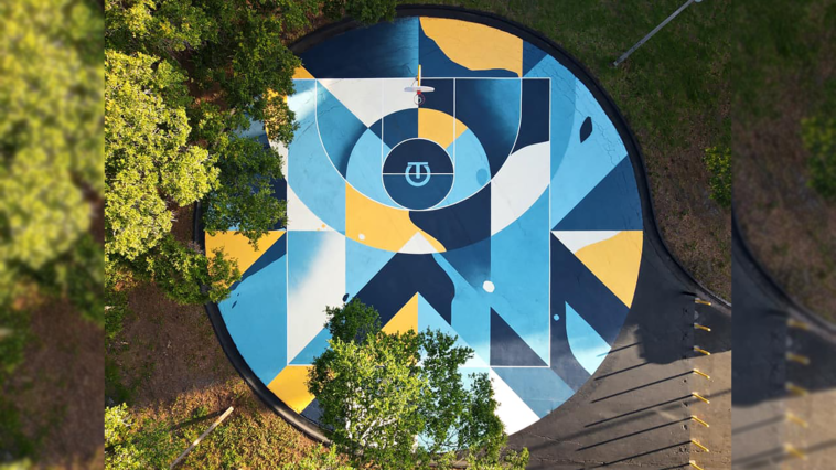 Aerial view of a blue and yellow mural on a basketball court