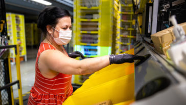 Employee wearing a mask and gloves sorting products in a warehouse
