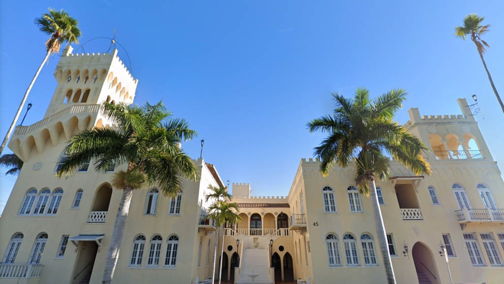 exterior of a historic castle-like structure with a bright yellow paint job and palm trees planted on either side