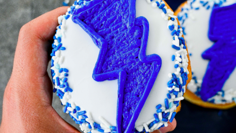 Phot of a vanilla froster donut with a blue lightning bolt on it