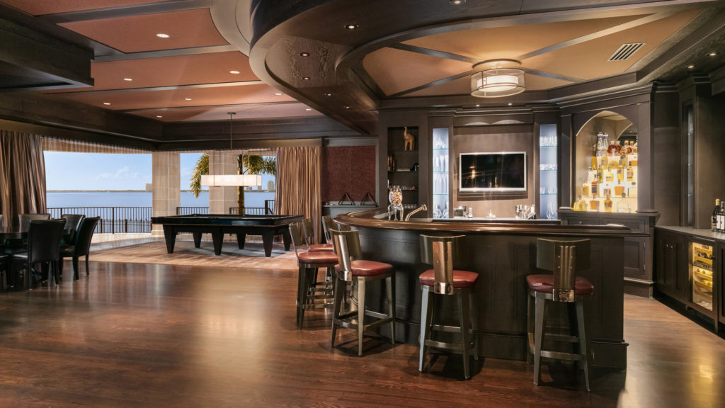 A private bar and pool table in a wood accented room in derek jeter's home