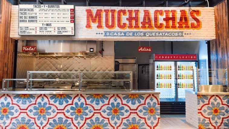 "Exterior of a restaurant with a hand painted sign reading ""Muchachas"""