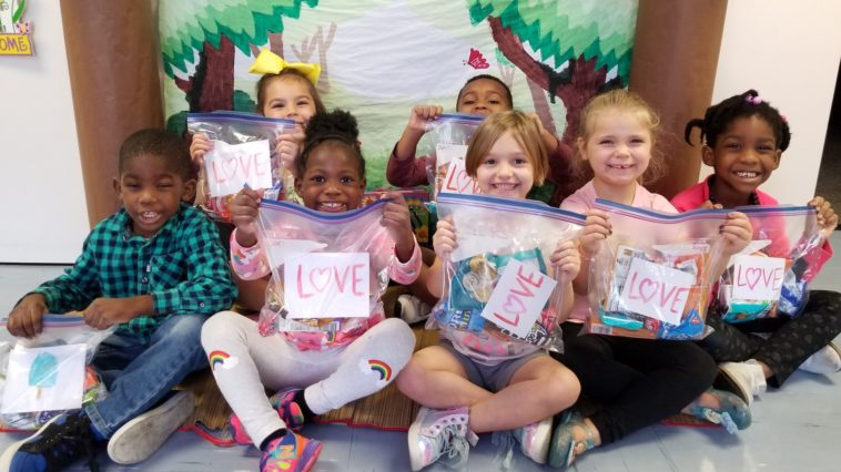 Photo fo young children holding goodie bags with LOVE written on the front