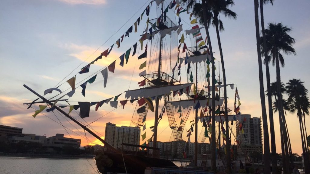 Photo of a tall pirate ship at sunset