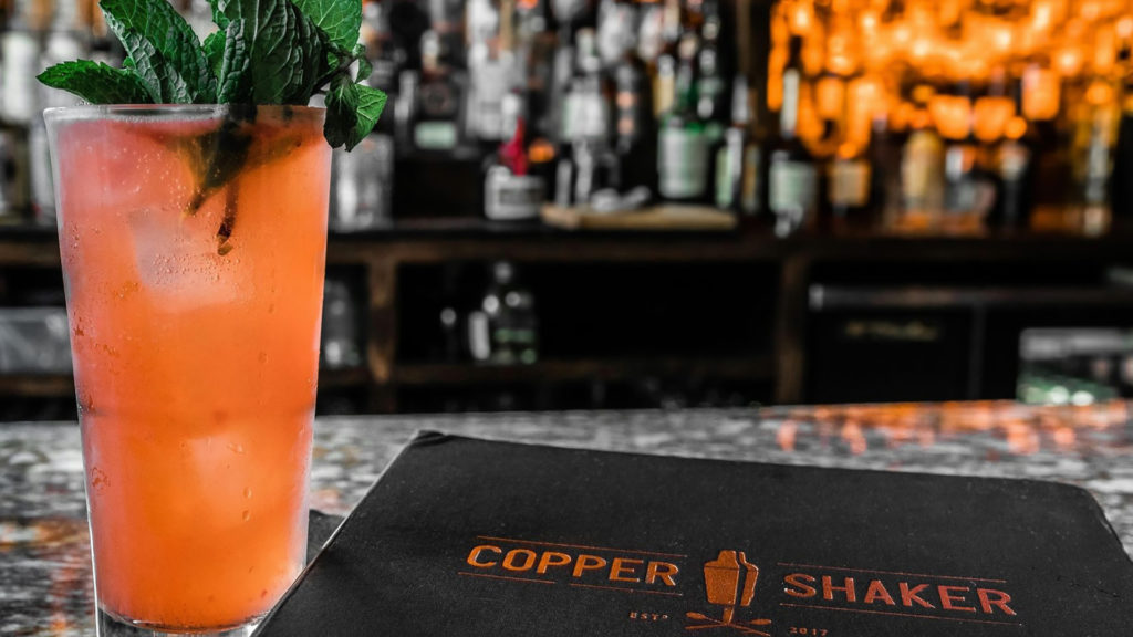 Interior of a bar with an orange cocktail to the left of a leather menu