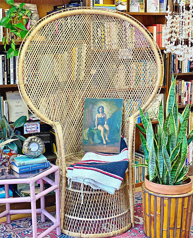 Large wicker chair with a blanket and a painting in the seat.