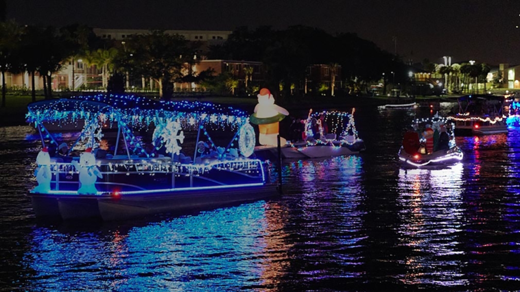 Photo of boats covered in holiday lights