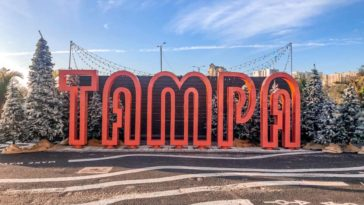 Image of a giant pink Tampa sign surrounded by Christmas trees