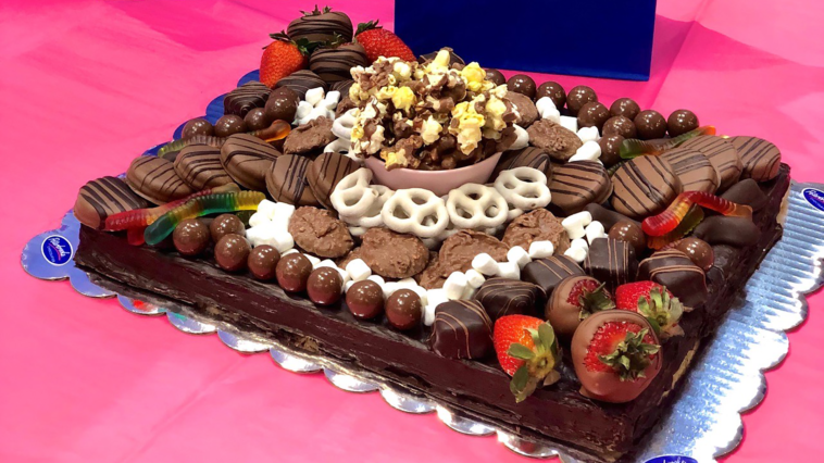 assorted chocolates, Oreos and pretzels arranged on a chocolate board