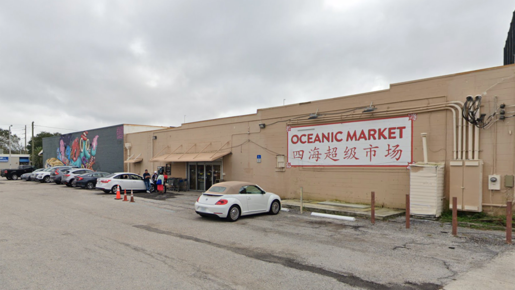 """Exterior of a supermarket with """"Oceanic"""" written in red on the front"""