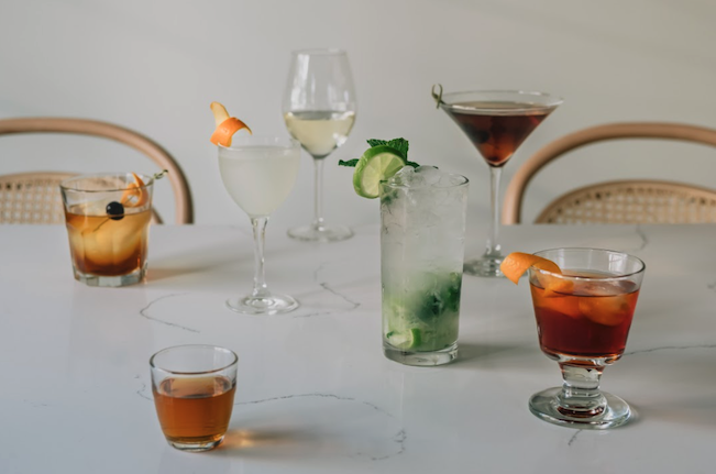 Assortment of craft cocktails in scotch, wine, and martini glasses.