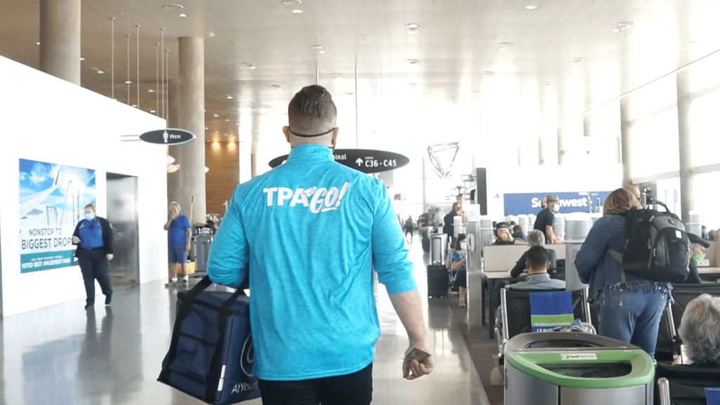 man in a light blue jacket carrying a bag of food in a airport terminal