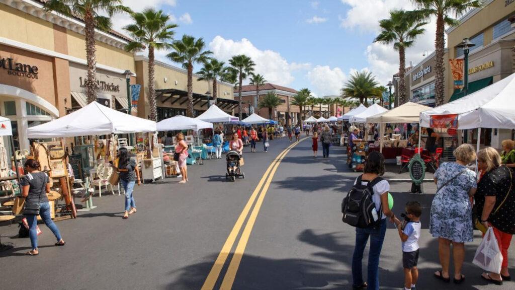 A street market featuring dozens of art vendors under white tents