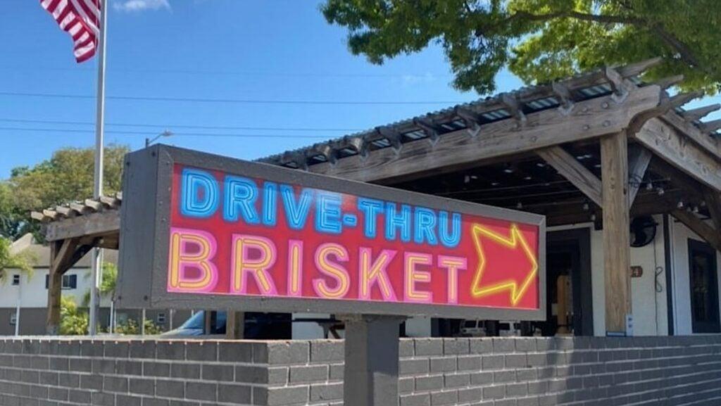 a drive thru sign outside a brick building