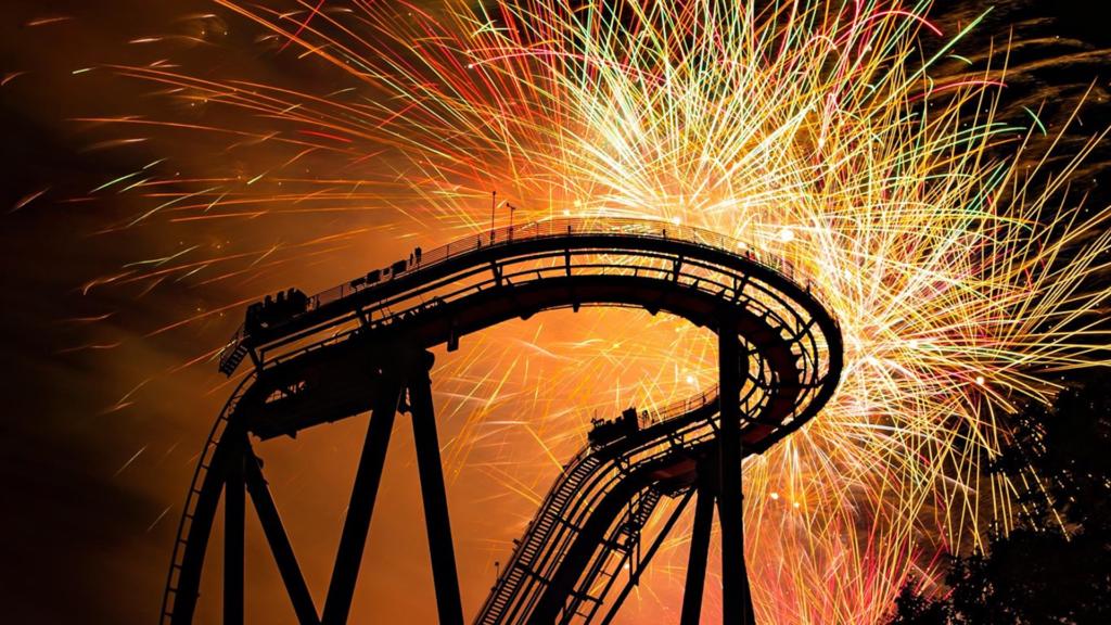 Fireworks display over a roller coaster