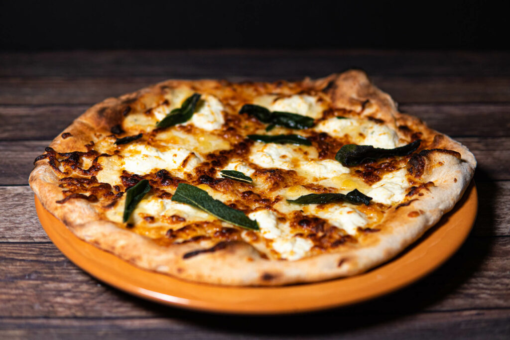 large pizza with basil leaves