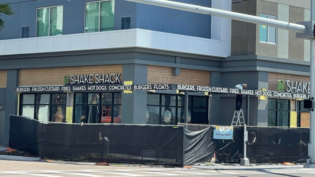 exterior of a ground floor shake shack with construction fencing around front