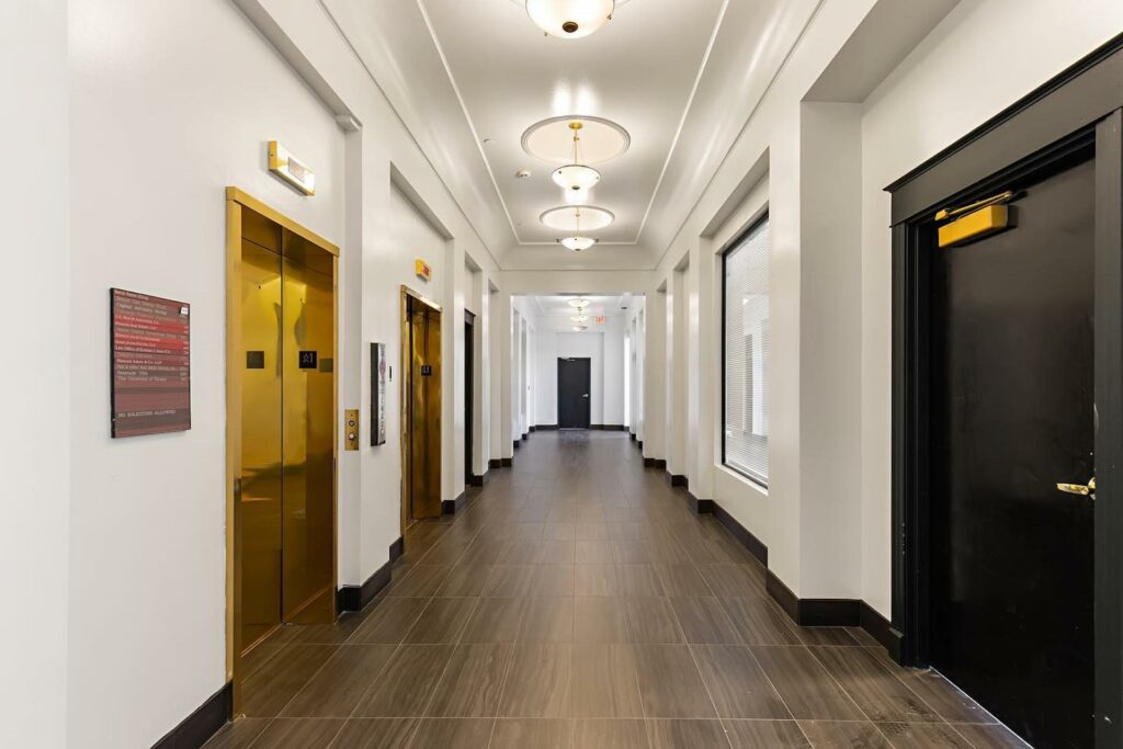 a long hallway featuring gold elevator doors and entrances to private offices