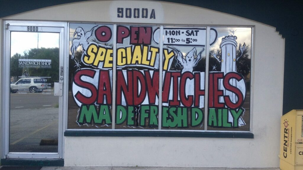 exterior of a small deli with a mural on the window