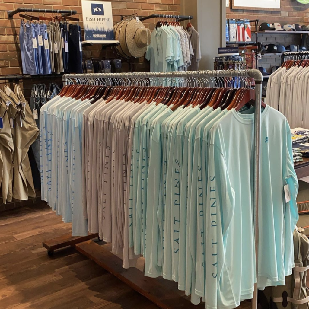 Rack of blue, tan, and teal long sleeved shirts with logos.