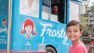 blue ice cream cart wit ha big Wendy's logo on the side