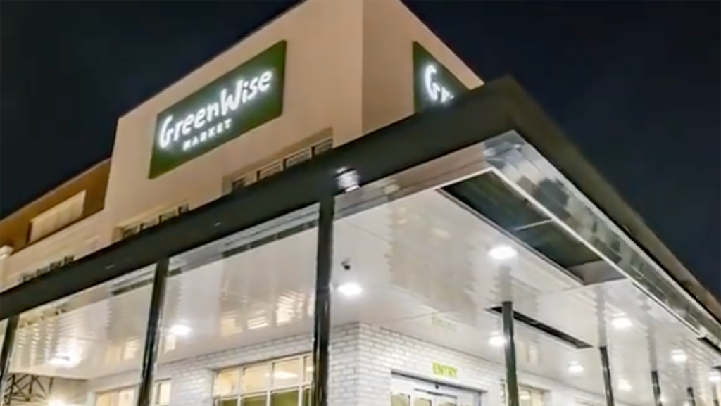 """exterior of a grocery store at night with a green """"Greenwise"""" sign"""