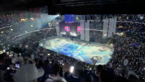 inside a hockey rink with blue and white lights flashing on the ice